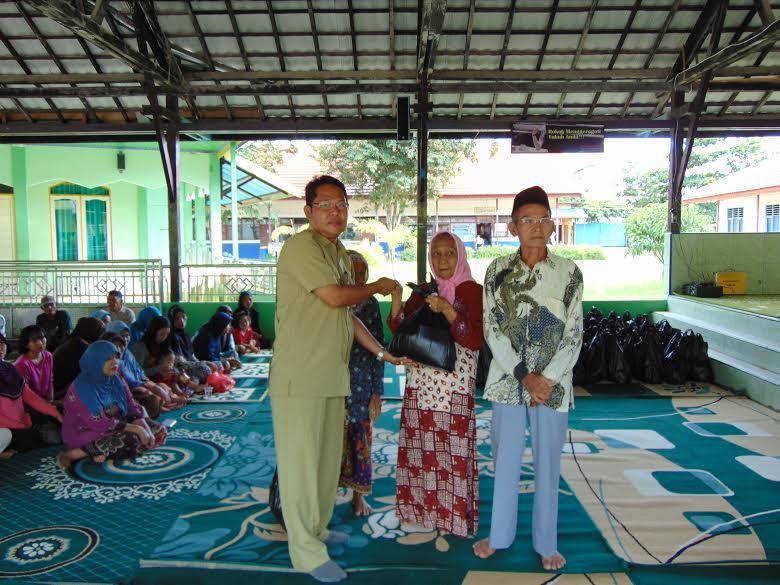 Penyerahan secara simbolis oleh Kepsek SMP Negeri 1 Kotabaru kepada warga pada pembagian paket Ramadhan (foto deddy)