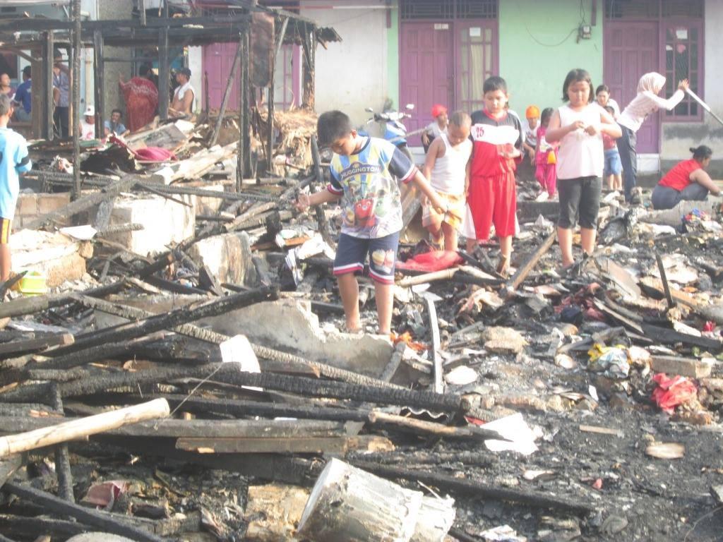 anak-anak kecil nampak mencari barang milik mereka yang masih bsa diselamatkan